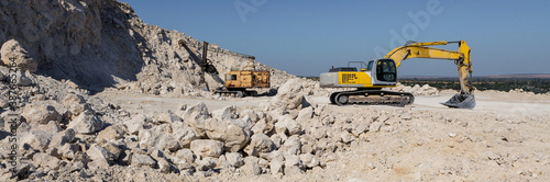 Fototapeta A large yellow tracked excavator is mining rock in a quarry.