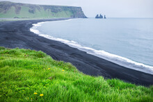 Myrdal, Iceland View Of Reynisfjara Black Sand Beach And Volcanic Rocky Cliff Formations With Seashore Coastline And Waves Crashing With Green Lush Plants