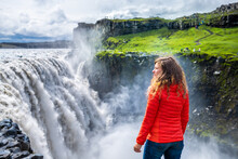 Young Woman Back Looking At Dettifoss Waterfall On Rocks Water Flowing Mist Spraying Cloudy Day In Iceland With Orange Jacket And Jeans