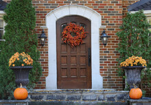 Wooden Front Door Of Brick House With Fall Decorative Wreath And Pumpkins