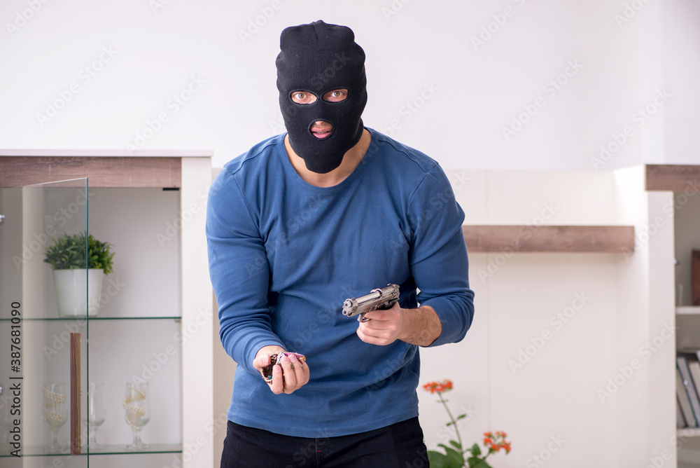 Fototapeta Male robber stealing valuable things from the house