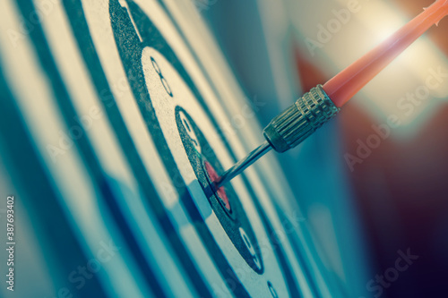 Obraz na plátně Bulls eye or dart board has red dart arrow throw hitting the center of a shooting target for business targeting and winning goals business concepts