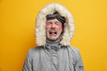 Dejected Man Cries And Feels Unhappy Dressed In Winter Clothes Feels Very Cold After Snowboarding Has Red Face Covered With Hoarfrost Wears Ski Goggles Isolated Over Yellow Wall. Recreation Concept