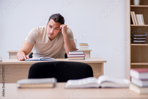 Obraz Young male student preparing for exams at library - fototapety do salonu