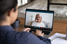 Rear View Of Female Employee Have Webcam Digital Virtual Conference With Mature Colleague Or Coworker. Woman Workers Speak Talk On Video Call At Home Office, Engaged In Online Team Meeting On Laptop.