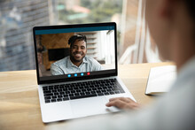 Close Up Rear View Of Woman Look At Laptop Screen Speak Talk On Video Call With Smiling African American Male Friend Or Colleague. Person Have Webcam Virtual Digital Conference With Ethnic Man Online.