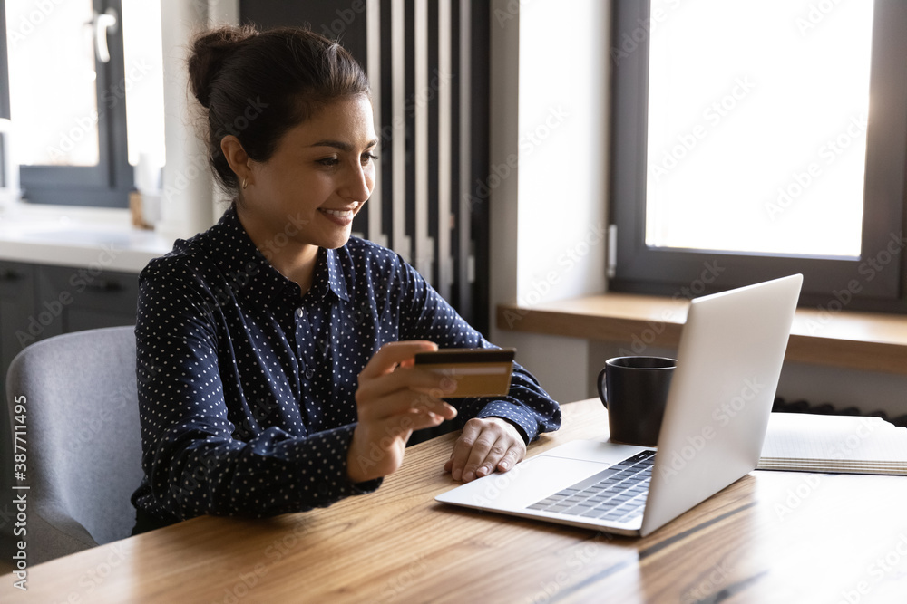 Fototapeta Smiling millennial Indian woman sit at home look at laptop screen shopping online on laptop with credit card. Happy young ethnic female make payment purchase on internet use secure bank system.