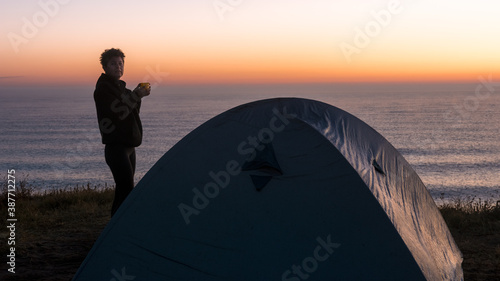 Woman at the seaside drinks her coffee at sunrise near the tent