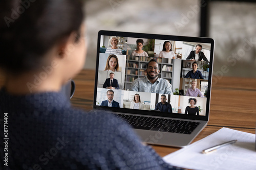 Over shoulder view of female worker have webcam digital virtual conference with diverse multiethnic colleagues. Woman speak talk on video call with multiracial businesspeople. Online meeting concept. - 387714404