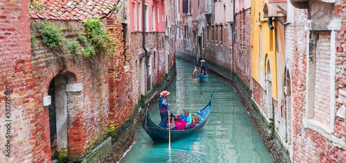 Fototapeta Venetian gondolier punting gondola through green canal waters of Venice Italy