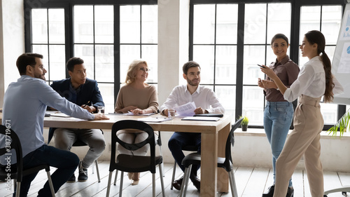 Confident multiethnic female trainers make flip chart presentation for diverse employees at office meeting Billede på lærred