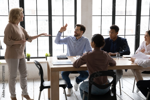Fotografija Smiling Caucasian male employee raise hand ask answer question at meeting with middle-aged businesswoman or CEO