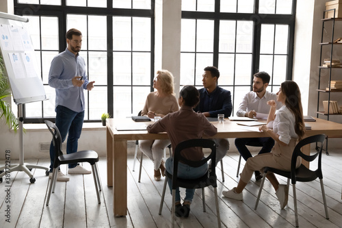 Fototapeta Confident young male speaker or coach stand make flip chart presentation for diverse colleagues in office. Businessman talk present business project on whiteboard for workers at meeting or training. obraz