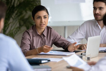Multiracial Businesspeople Talk Brainstorm At Office Meeting Together, Discuss Business Ideas In Group. Motivated Multiethnic Diverse Employees Cooperate Negotiate At Team Briefing At Workplace.