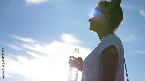 Fotografia Girl quench their thirst on a hot sunny day after a jog, drink water