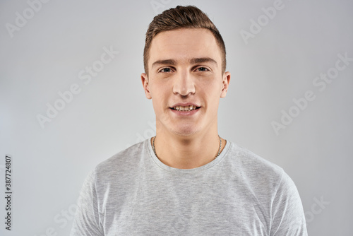 handsome man in light t-shirt cropped view emotion studio isolated background Canvas