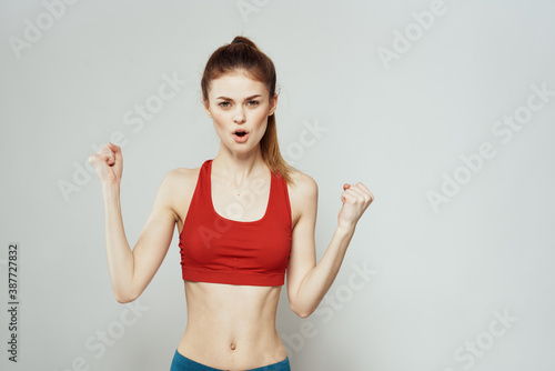 Obraz A woman in a red T-shirt on a light background is engaged in fitness gestures with her hands a slim figure  - fototapety do salonu