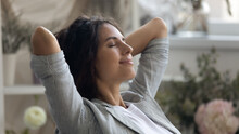 Close Up Of Young Caucasian Woman Rest Hands Over Head Daydream Or Visualize Relieve Negative Emotions. Happy Calm Millennial Female Relax With Eyes Close, Meditate Or Sleep. Stress Free Concept.