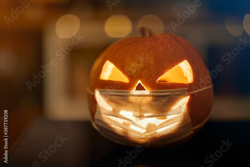 Halloween pumpkin with a carved face; Corona virus halloween concept - 387739208