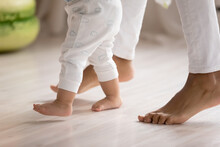 Crop Close Up Of Loving Mother Hold Little Biracial Child Hands Learn Walking At Home On Wooden Floor. Small Cute Ethnic Baby Toddler Make First Steps With Mom Support And Care. Childcare Concept.