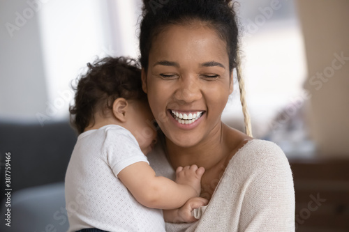 Fotografie, Obraz Close up of overjoyed young african American mom hold hug little biracial infant baby daughter