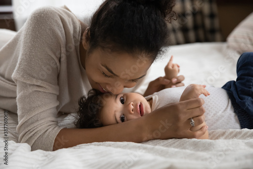 Fototapeta Portrait of loving happy young african American mother lying on bed with little baby infant kiss cuddle