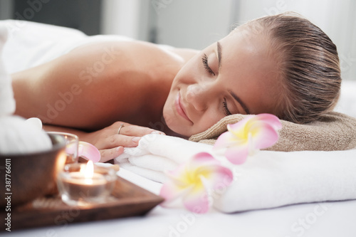 Obraz na plátně Smiling Caucasian woman in white  bath towel lie down and relaxing on bed prepar