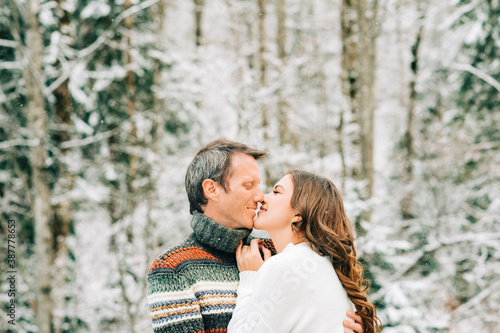 Valokuva Outdoor portrait of happy middle age couple kissing in winter forest