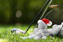 Festive-looking Golf Ball On Tee With Santa Claus' Hat On Top For Holiday Season On Golf Course Background..