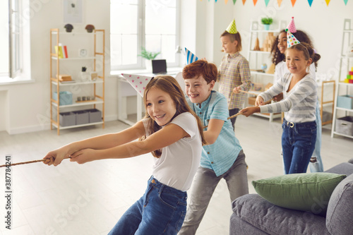 Obraz Happy children playing tug-of-war at fun party at home or in leisure club for kids - fototapety do salonu