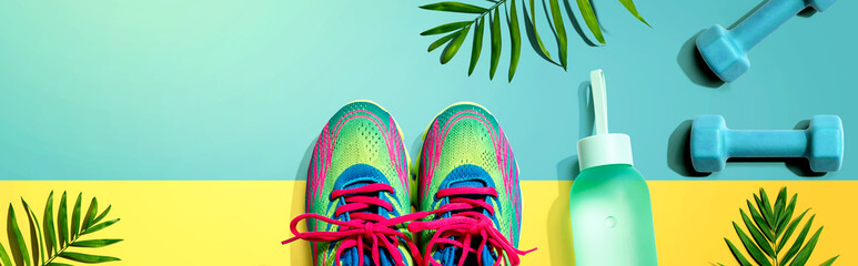 Fitness shoes and dumbbells with tropical plants - flat lay