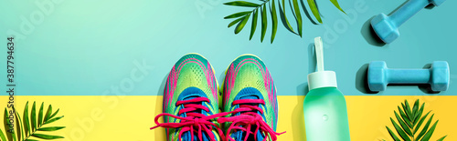 Fitness shoes and dumbbells with tropical plants - flat lay - 387794634