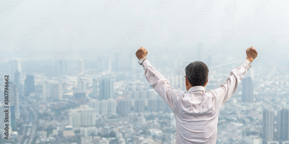 Fototapeta Business achievement or life-work balance success concept with happy senior businessman or retired elderly raising fists with ambition looking forward to city real estate building from rooftop