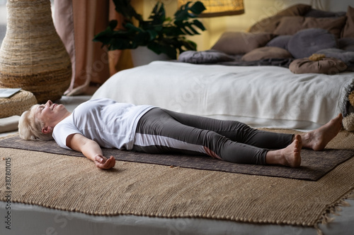 Canvas Senior caucasian woman lying on yoga mat after workout