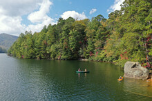 Aerial View Of Three Young Women Canoeing And Kayaking On Lake Santeetlah, North Carolina In Autumn.