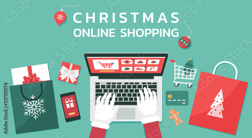 Obraz Christmas online shopping top view concept, Santa Claus hand makes order on laptop screen with gift boxes and shopping bags, and text, winter holidays sales, vector flat lay illustration - fototapety do salonu