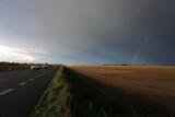 Samochody na drodze asfaltowej pośród póli tęcza na pochmurnym niebie.