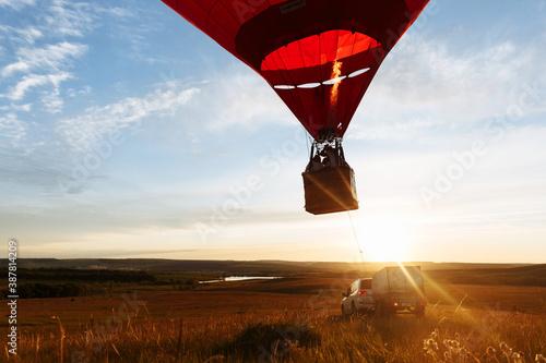 Obraz na plátne hot Red air balloon heart shape flying into sunset over valley landing or taking