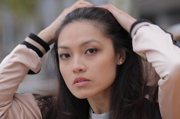 Young Asian woman poses for the camera in an urban area - people photography