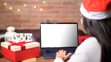 Young Smiling Woman Wearing Red Santa Claus Hat Making Video Call On Social Network With Family And Friends On Christmas Day. Laptop Monitor Screen Mock Up.