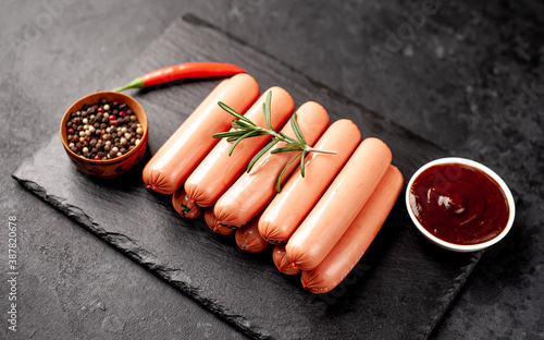 Fotografia raw classic sausages and sauce on a stone background