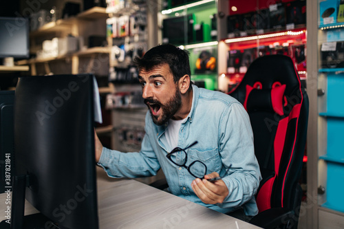 Excited young man choosing flat panel monitor for his home in an electronics store Wallpaper Mural