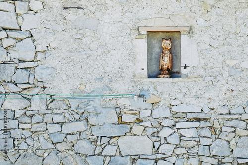 Tablou Canvas Sculpture en bois représentant un hibou posé sur un mur en pierre - Décoration d