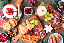 Christmas Theme Charcuterie Table Scene Against A Dark Wood Background. Assortment Of Cheese And Meat Appetizers. Top View.