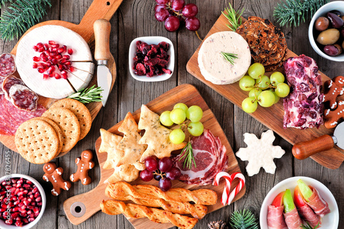 Christmas theme charcuterie table scene against a dark wood background. Assortment of cheese and meat appetizers. Top view. - 387826455