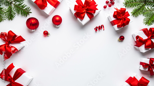 Obraz Merry Christmas and Happy Holidays greeting card, frame, banner. New Year. Noel. Red Christmas ornaments and gift on white background top view. Winter xmas holiday theme. Flat lay	  - fototapety do salonu