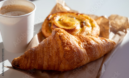 Fototapeta French breakfast in bakery served outdoor, cups of coffee and fresh baked croiss