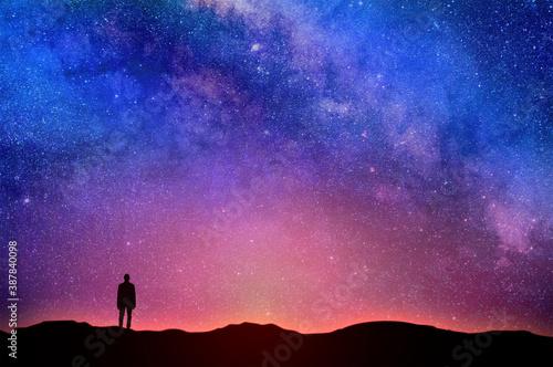 Valokuva Lonely man under night sky. Starry sky over the horizon
