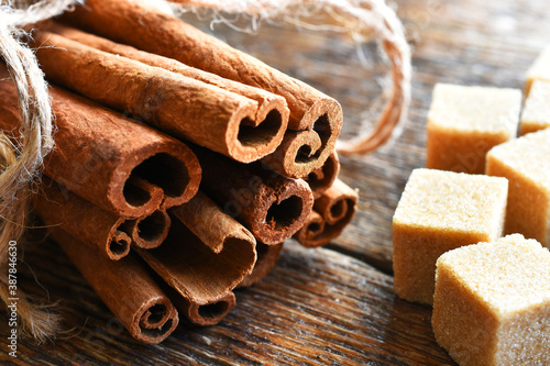 Fototapeta A close up image of fresh cinnamon sticks and brown sugar cubes.  obraz