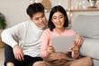 Leinwandbild Motiv Chinese Spouses Watching Movie Online Via Digital Tablet At Home